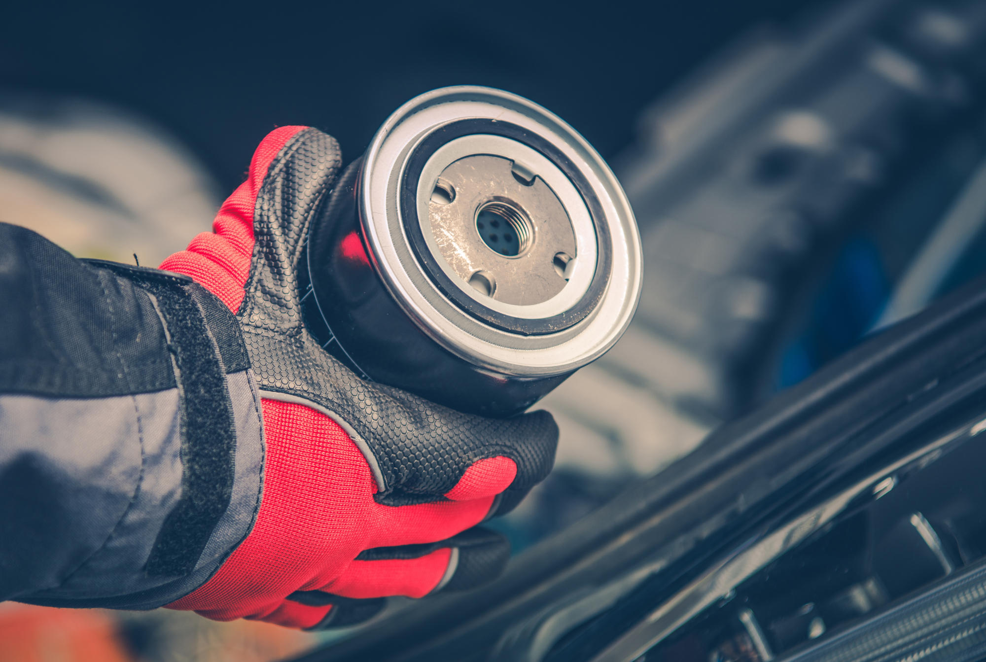 """Featured image for """"Best Oil Filter for Full Synthetic Oil"""" blog post. Oil filter in a mechanic's hand."""
