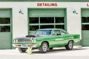Classic green muscle car with a guitar leaning on it in front of detailing shop.