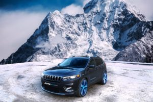 Black Jeep under a snowy mountain.