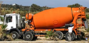 Large orange cement mixer truck.