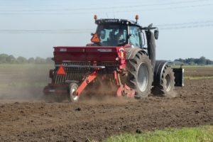 Tractor tilling soil.