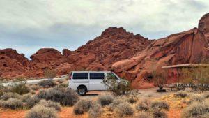 Van parked near desert shrubs.