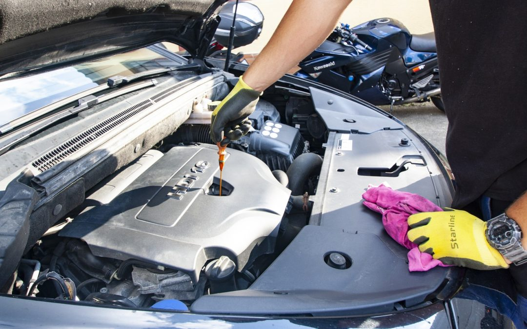 """Featured image for """"When to Switch to Synthetic Oil in a New Car"""" blog post. Repairing an engine."""