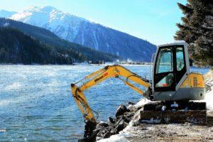 Excavator at a lake.