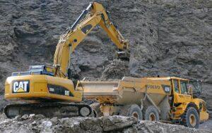 Excavator filling dump truck.